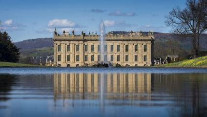 Front exterior shout of stately home Chatsworth House and the lake.
