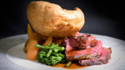 A plate a roast beef dinner with Yorkshire pudding and greens from the Lowry Hotel's The River Restaurant
