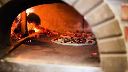 Fresh pizza in a clay pizza oven